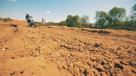autobike : Motorbike racer is crossing dusty terrain in a slow motion