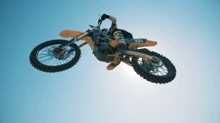 enduro : A motorcycler is flying over on his bike after jumping Stock Footage