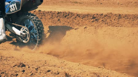 equipped : Motorbike is getting started by the rider in a dusty terrain. Stock Footage