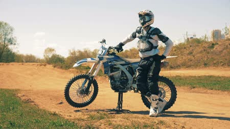 autobike : Motorcyclist and his autobike are standing in the middle of a dusty landscape