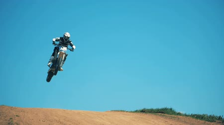 autobike : A leap of a motorcycler on his bike across dusty terrain