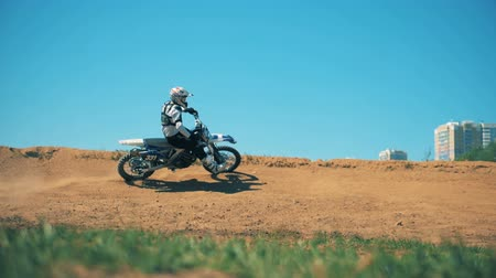 autobike : Professional motorcycler is driving across sandy terrain Stock Footage