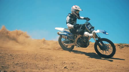 enduro : Motorcyclist is performing a trick while driving a motorbike through dust Stock Footage