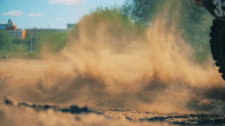 autobike : Close up of clouds of sand getting raised by a moving motorcycle Stock Footage