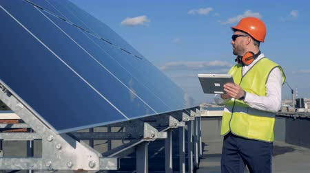 producing energy : Solar panels is getting checked by a male expert in workwear