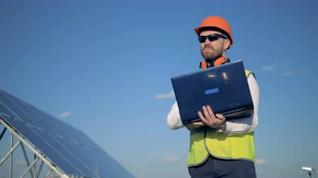 construtor : Male engineer is standing near solar battery and typing on his laptop. Alternative energy concept.