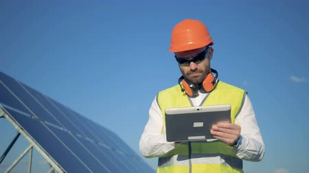inspector : Working process of a male inspector standing with a computer nearby the solar panel Stock Footage