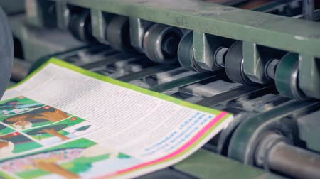 nakladatelství : Printed books go on a conveyor, close up.