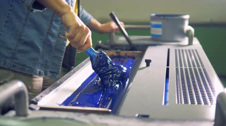 létesítmény : Male worker uses a brush to even a layer of a blue paint in a special section of a machine. 4K. Stock mozgókép