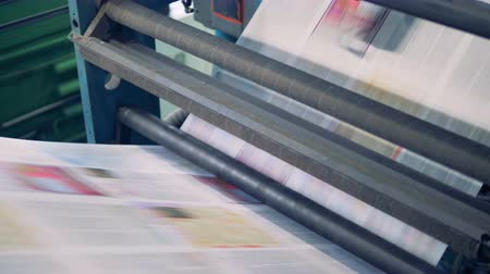 daily : Newspaper sheets on a conveyor, close up.