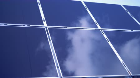 energetyka : The sky is reflecting on a surface of rectangular solar modules. Solar Panel Farm.