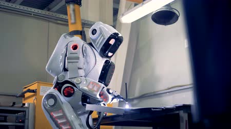spawacz : Industrial robot is standing in a factory unit and welding. Wideo