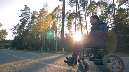 challenged : Disabled person in a powered wheelchair starts moving Stock Footage