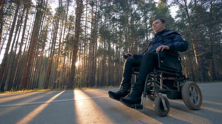 challenged : Physically challenged man is moving in a powered wheelchair along the road
