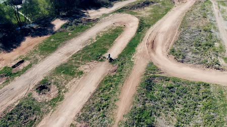 enduro : A racer is riding a motorbike through the hilly track