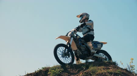 крайняя местности : Motocross participant with his motorbike on a hillock