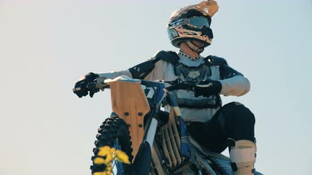rider : Equipped and prepared rider is sitting on his static motorcycle outdoors Stock Footage