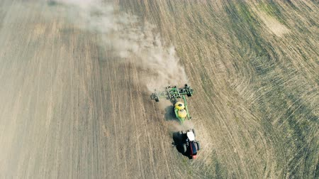 sowing : Working tractor sows the field, top view. Stock Footage