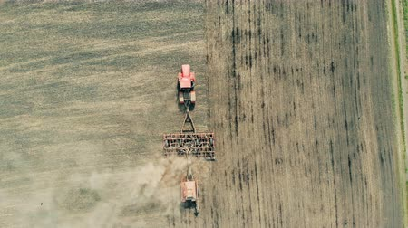 furrow : One machine works on a farmland, cultivating soil, top view.