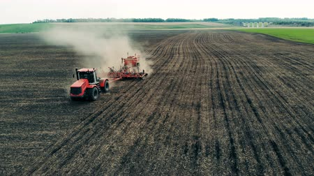 furrow : Red vehicle makes furrows for seeds on a farmland, top view.