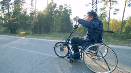challenged : Handicapped man moving along road in a training wheelchair. Recovery concept.