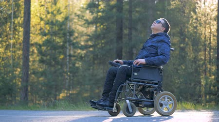 challenged : Handicapped person in a wheelchair is enjoying himself and surrounding nature