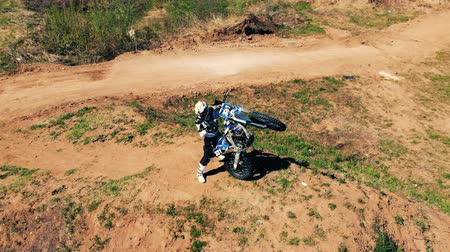 autobike : A rider is standing and vertically holding his motorcycle Stock Footage
