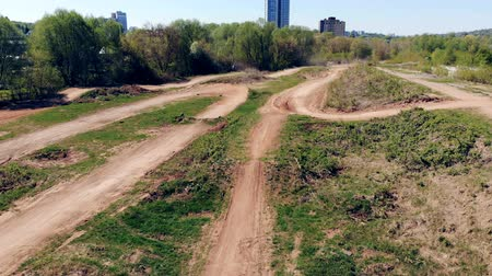 moto trials : Wide angle view of a race track with a racer driving through it on his motorcycle
