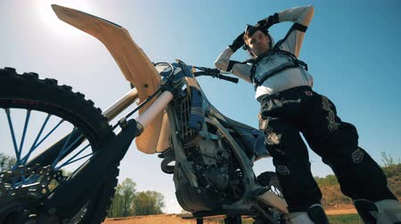 autobike : Motorcyclist is taking off his helmet and hanging it on his sportbike Stock Footage