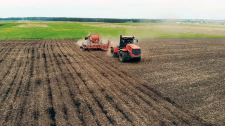 кампания : Healthy Food Production Concept. Tractor is sowing a spacious meadow with seeds. Aerial.