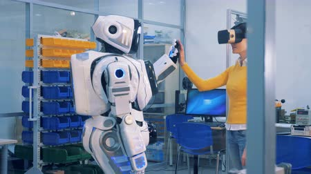 droid : A woman in VR glasses checks robot. Virtual reality game concept.