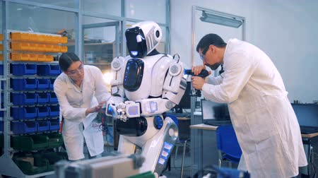 droid : Workers repair a robot in a laboratory room. Stock Footage