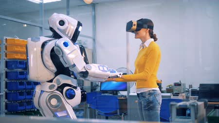 робот : A woman takes robots hands and looks around.