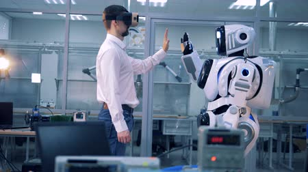 droid : A worker and a robot greet each other. Stock Footage