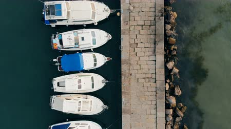 speedboats : Pier with a straight row of motorboats tied to it