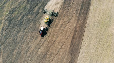 seeder : Top view of a plough sowing a massive field and raising dust
