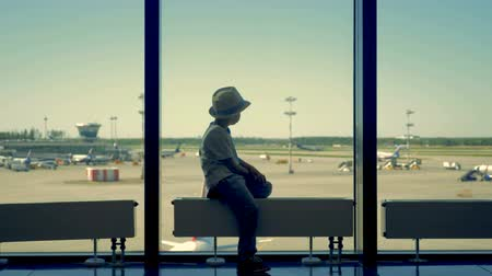 airfield : One child sits and looks at planes.