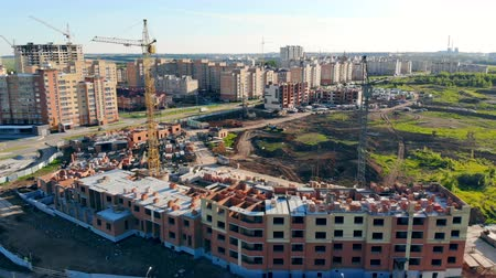 külvárosok : Building process on a construction site. Cranes build new houses on the city outskirts. Stock mozgókép