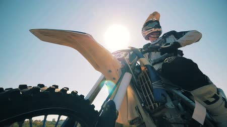 autobike : FMX rider is sitting on his motorbike against the sun