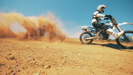 equipped : Motorcycler is riding through sand and raising clouds of dust