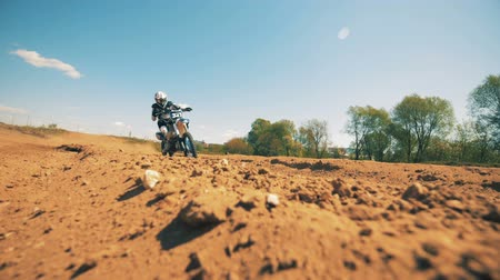 autobike : Slow motion footage of a motorcycler riding across dusty terrain. Slow motion Stock Footage