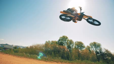 motorbike jump : Panoramic view of a racers jumping trick performed on a motorcycle. Slow motion