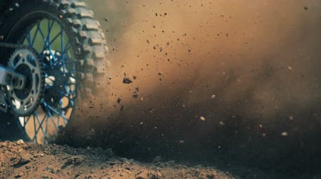 extreme : Close up of autobikes wheel starting motion and raising clouds of dust Stock Footage