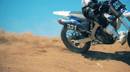 mekanizma : Motorbike is being driven across an offroad terrain. Slow motion