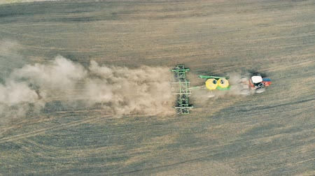 plough land : Sowing machine is scattering meadow with seeds in a view from above Stock Footage