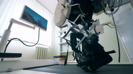 simulace : Close up of mans legs in bonds of a training machine during walking exercises. Electronic medical robotic for rehabilitation.
