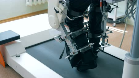 physically : Close up of legs of a male patient getting trained by a track machine