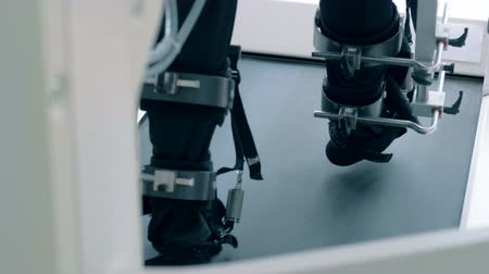 power equipment : Back view of fixated male feet walking along the simulation track Stock Footage