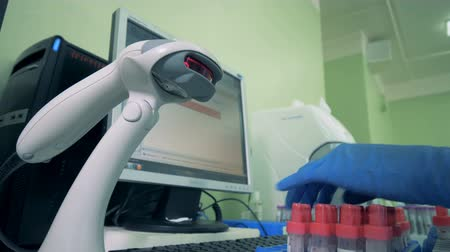 registration : Worker scans tubes with blood, close up.