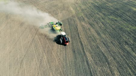 ploughing : Aerial view of an agriculture tractor moving across field. Healthy Food Production Concept. Stock Footage